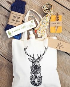 Groomsmen received screen-printed totes filled with manly must-haves, including J.Crew socks, Fox & Brie ties and pocket squares, Kiehl's lotion, and Izola olive oil soap sets.