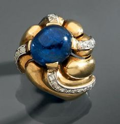 """SUZANNE Belperron Ring """"vortex"""" composed of seven twisted fluted yellow gold and platinum crimped at the center of a wide sapphire Cabocho ..."""