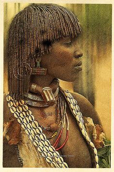 Ethiopian Hamar woman with her Nubian coils and jewelry coated with the red mud with which the Hamar women traditionally dress their hair.