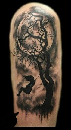 Ghastly yet enthralling monochrome arm tattoo. The design features a little girl playing by the swing which is tied to an old tree under the gaze of the moonlight.