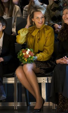 Queen Mathilde of Belgium made a statement wearing a mustard, pussy-bow blouse and high-waist skirt for her visit to the Antwerp Royal Conservatoire, School of Arts of the Artesis Plantijn Hogeschool.