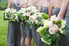 charcoal suits for the guys; girls wearing shades of green (clover/sage to emerald) and with very similar flowers