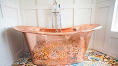 copper bathtub with patterned caustic floor tiles <3