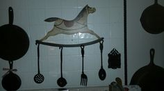 One day I was at an antique shop and spied a metal rocking horse with kitchen tools on it. I really wanted.it but with a price tag.of $85.00 it was oit of my reach. Last summer we were at a.flea.market and I spied the same.kind of kitchen tools on a single metal rack for $1.00. I was excited. Took them home and hu g them over my stove. This past week I was at a.consignment shop and saw this wooden  carousel wall hanging. Hubby drilled holes and put hooks on this for me. For $3.00 I got the…
