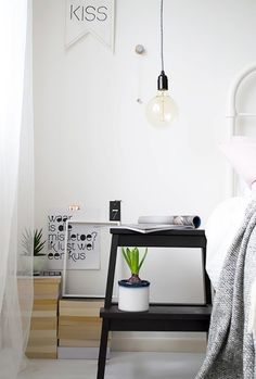 Bedroom with a low-hanging pendant light and an IKEA stool doubling as a nightstand