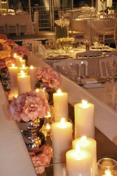 mirrors, candles, flowers and chrome finished ball vases.... Wedding flowers top table