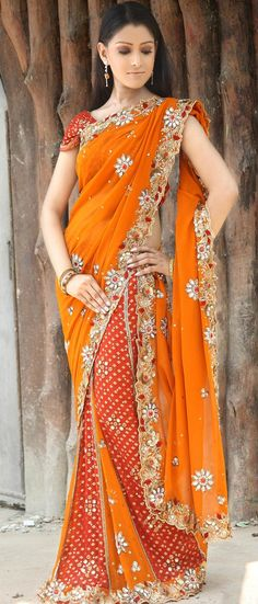 Deep Orange and red designer lehenga style faux georgette saree adorned with golden print at the lower part at the skirt pattern of saree highlighted with mirror work. Orange pallu is decorated with small booties all over. Border is designed with sequins, stones, zari, resham etc in pattern of flower and leaves creepers. Embroidered pallu is making this saree look gorgeous. Embroidered red color blouse is available with it. (There might be slight colour variation)