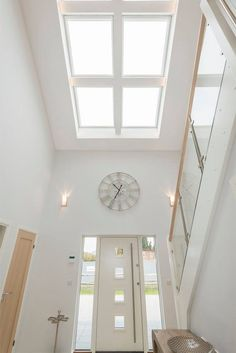 Velux Windows spotlights the white modern hallway of this timber frame house interior