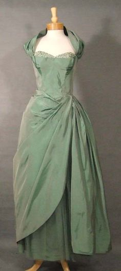 Vintage Clothing. Iridescent, rustling mint green taffeta gown. Fitted, strapless, boned bodice with pointed/basque style waist. Detachable shoulder wrap/halter strap. Shimmering iridescent sequins at the bust. The skirt is layer of taffeta, covered with 2 layers of tulle & topped with 2 panels of extraordinarily pleated & swagged taffeta.