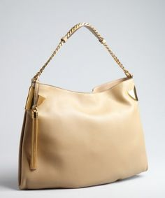 Superior designs by Gucci are the obvious choice for the bag-obsessed gal! Color: Beige Supple grained leather with polished goldtone hardware Side metal corners with subtle embossed logo Inset magnetic snap closure 16'' chain strap with leather shoulder detail, metal tassel, and 6'' drop Woven interior lining with side zip pocket and two organizational pockets Measures approximately 17'' at widest x 12'' tall at center x 1½'' deep; weighs 2 lbs.
