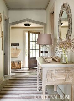 Two taupe and cream striped rugs are placed at right angles in the entryway and hall that connects the front of the house to the garden in the back in a home designed by Beth Webb . Image courtesy Traditional Home.