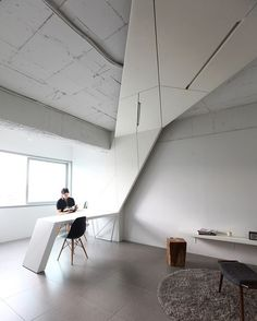 For this live-work space in the heart of Seoul, AnLstudio incorporated a versatile airplane wing-like ceiling system outfitted with LEDs. The system extends throughout the studio and terminates as a sleek workstation complemented by black Eames chairs. : Sunghwan Yoon. #architecture #interior #design #interiordesign #seoul #apartment #studio... - Interior Design Ideas, Interior Decor and Designs, Home Design Inspiration, Room Design Ideas, Interior Decorating, Furniture And Accessories