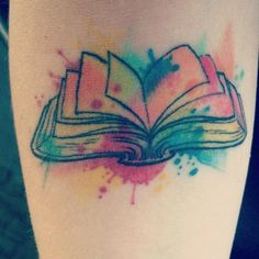 an open book with pages lifted, surrounded by splotches of pastel watercolor