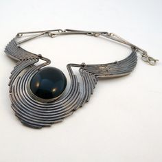 """Vintage Necklace   Patricia Allebrand.  """"Jewelry is a sculpture that is more intimately involved with the people that wear it"""" she explains. Beautifully crafted sterling and onyx necklace. The solid sterling silver artistically wraps in waves around the black stone. The chain measures 18"""" and the pendant drops 4 1/2"""" for a total length of 22 1/2"""". The stone measures 1 1/4"""" by 3/4""""."""