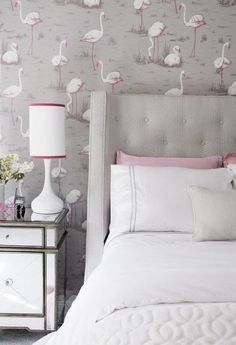 Sat against a Cole & Son Flamingos Wallpaper covered wall, a gray tufted wingback headboard supports a bed dressed in white and gray pearl beaded bedding topped with white shams sat in front of light pink shams while beside the bed a mirrored nightstand is accented with a white table lamp finished with a white shade with a pink border in this beautiful contemporary teen girl's bedroom.