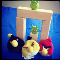 Angry Birds Carnival Game...simple but a huge hit with kids...throw the plush birds at the blocks, one at a time. 3 tickets, 3 tries to knock over the pigs and blocks. Knock over all the blocks, win a bigger prize. Tape floor off for starting point..younger kids closer and older kids about 8 ft. away. Tape off 2 lanes for double traffic. Have fun!!