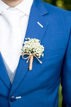 The groom's boutonniere is simply made of baby breaths and wrapped in rope.