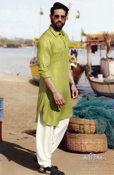 Pathani Kurta suits are characterized with long (Knee-length or bit longer) Kurtas and a loose Salwar. Apart from the obvious fact the Pathanis are extremely comfortable, they also add masculinity to the overall personality. Pathani Kurta Men, Pathani For Men, Designer Suits For Men, Designer Clothes For Men, Mens Shalwar Kameez, Kurta Pajama Men, Gents Kurta, Indian Groom Wear, Indian Wear