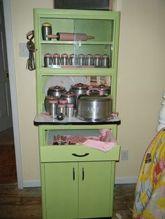 Collection of pink Kromex displayed on a mint colored metal hoosier cabinet.