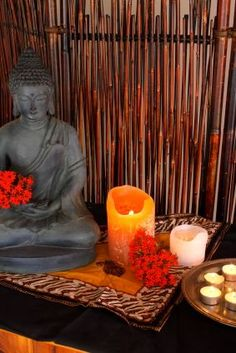 Buddha, flowers and candles set in a natural backdrop. Very zen.