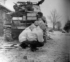 """American soldiers in the Battle of the Ardennes under cover M4 """"Sherman"""" medium tank"""