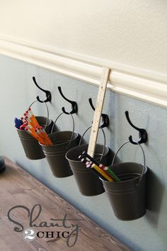 Art supply storage with buckets and hooks!  I did something similar to this in my daughters room around her desk, except used peg board.  Think it turned out cute. (totally think I could use these for hair stuff and other odds and ends) !