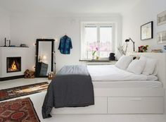 White Scandinavian bedroom warmed by the cosy fireplace