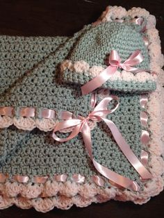Crochet baby blanket. Gray with pink trim and pink satin ribbon insert. Includes matching hat.