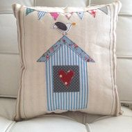 Lovely ticking cushion with a shabby beach hut and naughty seagull on top! Centre panel can either have an organic cotton heart (as pictured) or something personal to you, such as a house number, any ideas welcome! Cushion is filled with safety compli...