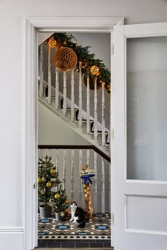 A beautiful townhouse makes for a glamourous and festive family home in the south of London. It is here where modern glamour meets industrial living with a fascinating mix of textures and deep tones that give this home depth and soul. Small Christmas Trees, Christmas Time, Christmas 2016, Festival Decorations, Xmas Decorations, Seasonal Decor, Holiday Decor, Stair Decor, Christmas Fireplace