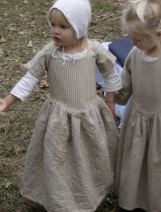 Child in Mill Farm Girl's Gown of natural stripe linsey woolsey.