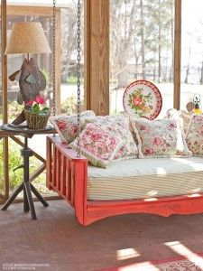 Comfy couch swing on porch with decorative throw pillows