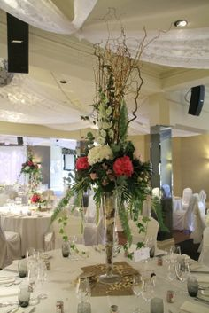 Majestic and tall vases of Autumn branches surrounded by Roses and Hydrangeas dressed the tables in the Banqueting suite