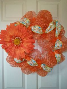 Sum-sum-summertime!!!   Orange oasis mesh with orange, teal, and yellow ribbon entwined and a humongous Gerbera daisy!