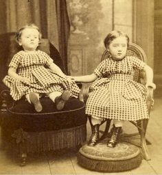 Memento mori photo. Twin poses with deceased sister (left). Memento mori's were popular in the Victorian era, photographs were expensive back then and the child death rate was high, so a lot of times this photo was the only one a family had to remember the deceased by. Usually purchased as a gift for the grieving families.