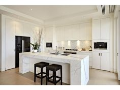White kitchen with calcatta wrapped central island