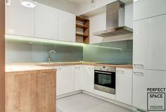 Klasyczna kuchnia z białymi frontami szafek z drewnianymi elementami. Oświetlenie LED nad blatem kuchennym. Backsplash w pistacjowym kolorze.