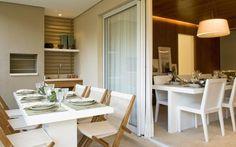 Na varanda do apartamento decorado pela arquiteta Fernanda Marques há lugar para churrasqueira e uma mesa de refeições anexa à sala de jantar