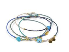 beautiful gold plated bangle bracelets with denim color silk and small charms. www.sophisticatedgold.nl