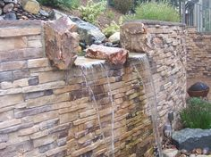 Retaining wall w/ a stone facade and waterfall. Love it!