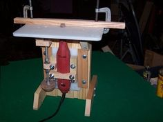 Dremel Router Table by RustyL -- Homemade Dremel router table constructed from wood, plastic cutting boards, threaded rod, nuts, and bolts. http://www.homemadetools.net/homemade-dremel-router-table