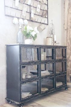vintage pieces - old metal cup rack and apothecary cabinet repurposed as dining room hutch.