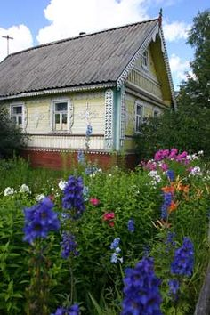 Russian country cottage foregrounded by a lovely perennial garden.