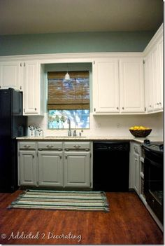 Kitchen. Colored bottom cabinets and white on top with black appliances.