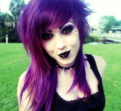This is a simple Goth teen girl, with straight, dark purple hair. She wears a simple black top, complete with a studded choker, multiple piercings, and traditional Gothic make-up. Note her pale skin and beauty mark.