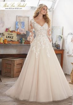 Style LNXZ Maira Wedding Dress Long Sleeve Wedding Dress Featuring Delicate Crystal Beading on Bodice and Embroidered AppliquéŽs on Tulle. V-Neckline and Open Keyhole Back. Colors Available: White, Ivory, Ivory/Caramel. Shown in Ivory/Caramel.