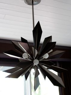In addition to illuminating the space, sculptural lighting can double as art. In this midcentury modern basement, a striking starburst fixture made of smoked chrome beautifully reflects light during the day, and after dark, its modern globe bulbs keep the area brightly lit.