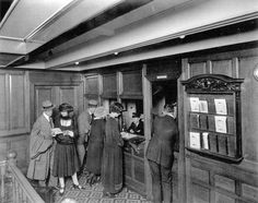 Second class passengers gathering at the Second Class Purser's Office aboard the RMS Olympic.  On the Titanic this area would have been identical. Located on E-Deck and adjacent to the Aft Second Class Staircase (part of the railing can be seen in the bottom-left), this purser's office offered several services to second class passengers such as answering inquiries, storing valuables in their two safes, and receiving passengers' letters.