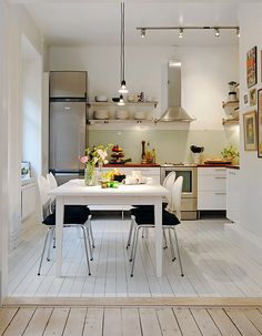 White hardwood floors in kitchen. Transition from natural hardwood in next room.