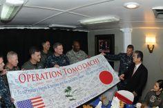 トモダチ作戦  US military aboard USS Ronald Reagan present Japanese official with special banner.